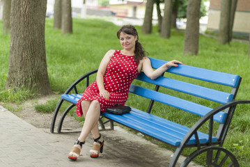 Beautiful girl on a bench in the park.