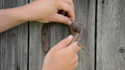 closeup hand hammer retro rusty horse shoe on wooden house wall