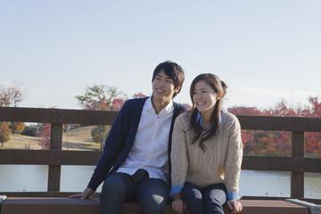 公園のベンチで座るカップル