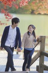 紅葉の公園の階段をのぼるカップル