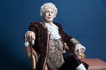 Retro baroque man with white wig holding a walking stick sitting
