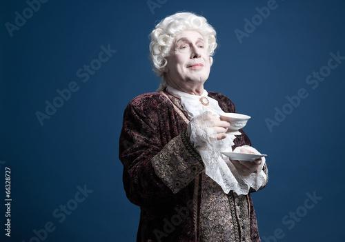 Smiling retro baroque man with white wig holding a porcelain tea - 66328727