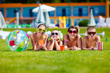 group of happy teenage friends lying on summer lawn