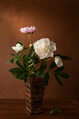A  bouquet of peonies in wooden vase.