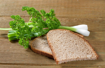 Black bread with green onions on a wooden background.
