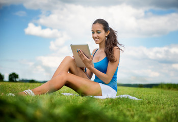 Beautiful woman using a tablet sitting on meadow