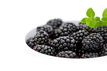 White bowl with pile of fresh blackberries and green mint