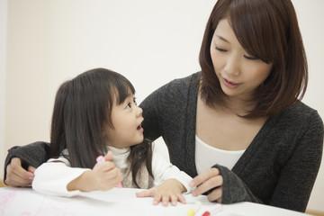 部屋でお絵描きをする母と子