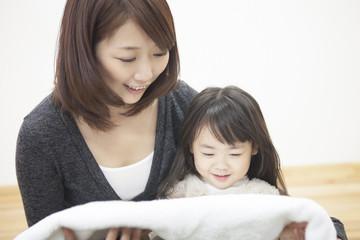 タオルをたたむ母と子