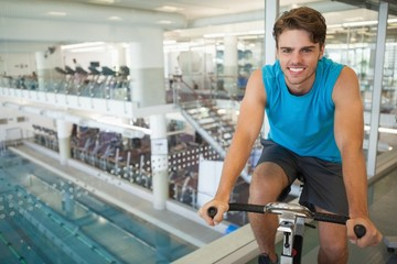 Smiling fit man on the spin bike