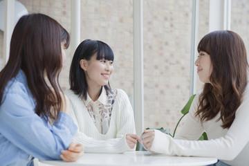 座って3人で談笑する女子学生