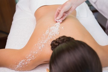 Beauty therapist pouring salt scrub on womans back