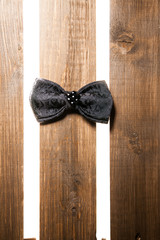 Black handmade bow tie over wooden background