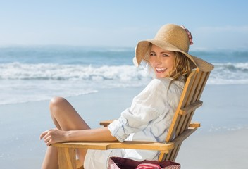 Smiling blonde sitting on wooden deck chair by the sea