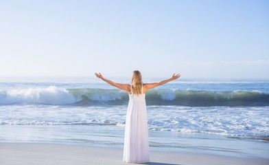 Blonde standing at the beach in white sundress with arms out