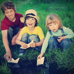 three boy play in  stream