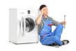 Pensive plumber fixing a washing machine