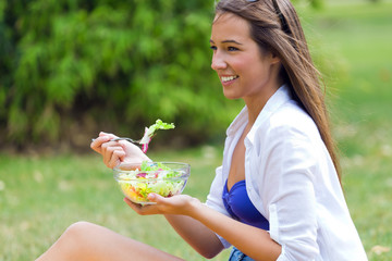 Beautiful young woman holding green salad, outdoors