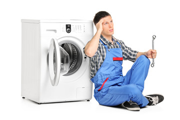 Pensive plumber fixing a washing machine