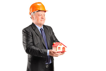 Mature architect holding a small model house