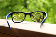 eyeglasses in the hand over blurred tree background - 66333748