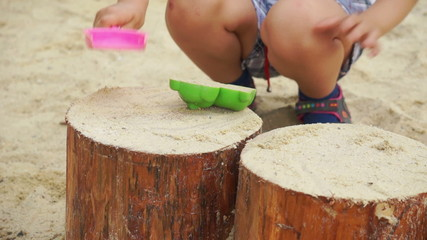 Child plays in a sandbox.