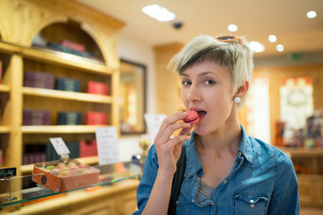 Young blonde woman portrait eating the french pastry macaron ins