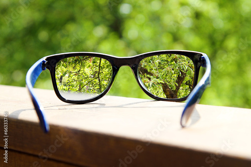 Leinwanddruck Bild eyeglasses in the hand over blurred tree background