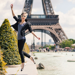 Young blonde woman portrait jumping in front of the Eiffel Tower