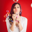 Beautiful woman portrait with soap bubble against colorful red b