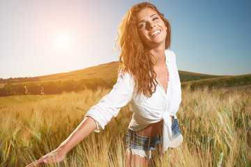 Young, beautiful woman in a wheat field. Tuscany, Italy