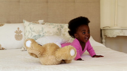 Cute baby girl playing with teddy bear on bed