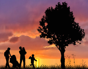 family and tree silhouettes at sunset