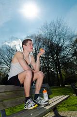 sportler sitzt auf einer parkbank