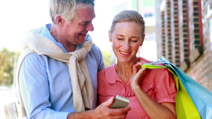 Happy couple looking at smartphone together on shopping trip