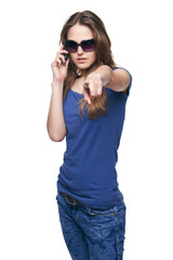 Young woman pointing at camera while talking on cell phone