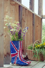 Wild flowers in Union Jack rubber boots-wellies on a country hou