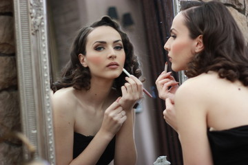 Beautiful vintage retro woman looking in mirror