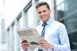 Cheerful entrepreneur reading newspaper