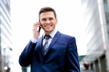 Smiling man in suit talking on cell phone
