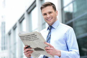 Cheerful entrepreneur reading newspaper