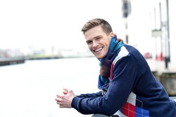 Stylish young man beside river railing