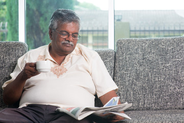 Indian senior adult drinking coffee while reading news paper