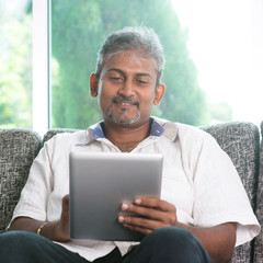 Indian man using digital tablet computer