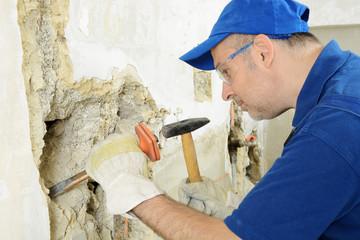 Handwerker arbeitet mit Hammer und Meissel