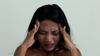 A woman with a headache holding head