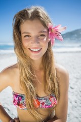 Beautiful smiling blonde with flower hair accessory on the beach