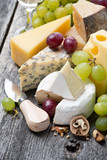 assortment of fresh cheeses, grapes and walnuts