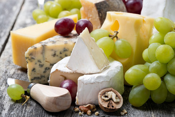 assortment of fresh cheeses and grapes on a wooden background