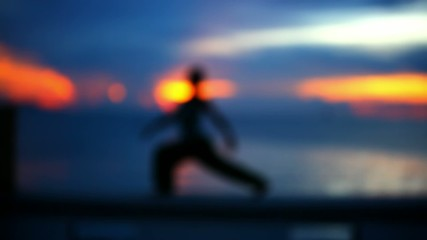 Girl doing yoga at sunset. Blurred background. Video